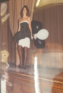 Model in black and white dress, holding black and white balloons.