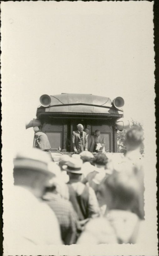 Black and white photograph showing a man standing on on a train car, speaking into a mcirophone. In the foreground is a crowd of people facing away from the camera and toward the man on the train. The men are wearing overalls and straw hats. There are also women in the crowd.