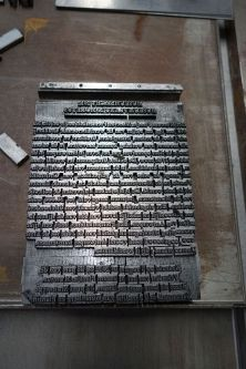 Photograph of lines of type forming a page from which to print.