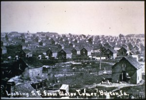 Black and white photograph showing a broad, open area with many houses set in plots of land.