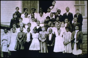 Black and white photograph of schoolchildren lined up in five rows in front of a school building. At the back is a teacher. The children are both male and female. A large portion are black, while the rest are white. The teacher is female and may be black.