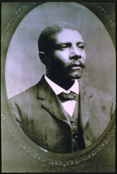Black and white portrait of a Black man wearing a suit jacket, vest, shirt and bow tie. Photogaph is in an oval frame.