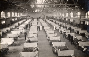Black and white photo of a large gym acting as a hospital ward. Beds with patients fill the entire space in six rows. Cloth barriers are set up between each bed. Nurses and men in uniform wearing masks across their nose and mouth stand throughout the room.