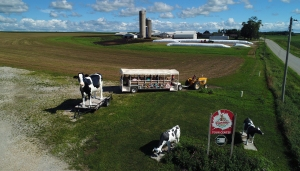 """Farm with silos and farm buildings surrounded by empty fields form the background and middle-ground. In the foreground is a sign reading """"Hansen's Dairy Tour Center"""" and a tractor pulling a trailer loaded with people in seats."""