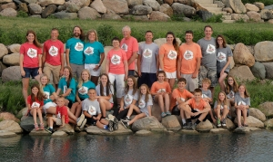 Family portrait of 3 generations wearing color coordinated Hansen's Dairy t-shirts showing nuclear families. In the center at the back are a man and woman (grandparents) with their adult children and spouses on either side. Seated in front are 16 children.