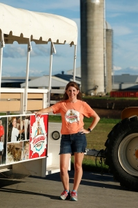 Woman standing next to an open trailer with seats for people to sit in that is attached to a tractor. In the background is a farm with two silos and other farm buildings.