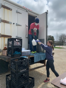 A person wearing a face mask stands in the back of a delivery truck and hands a gallon carton of milk and another product to another person standing on the ground who is also wearing a face mask. The truck appears to be in a parking lot within a town.