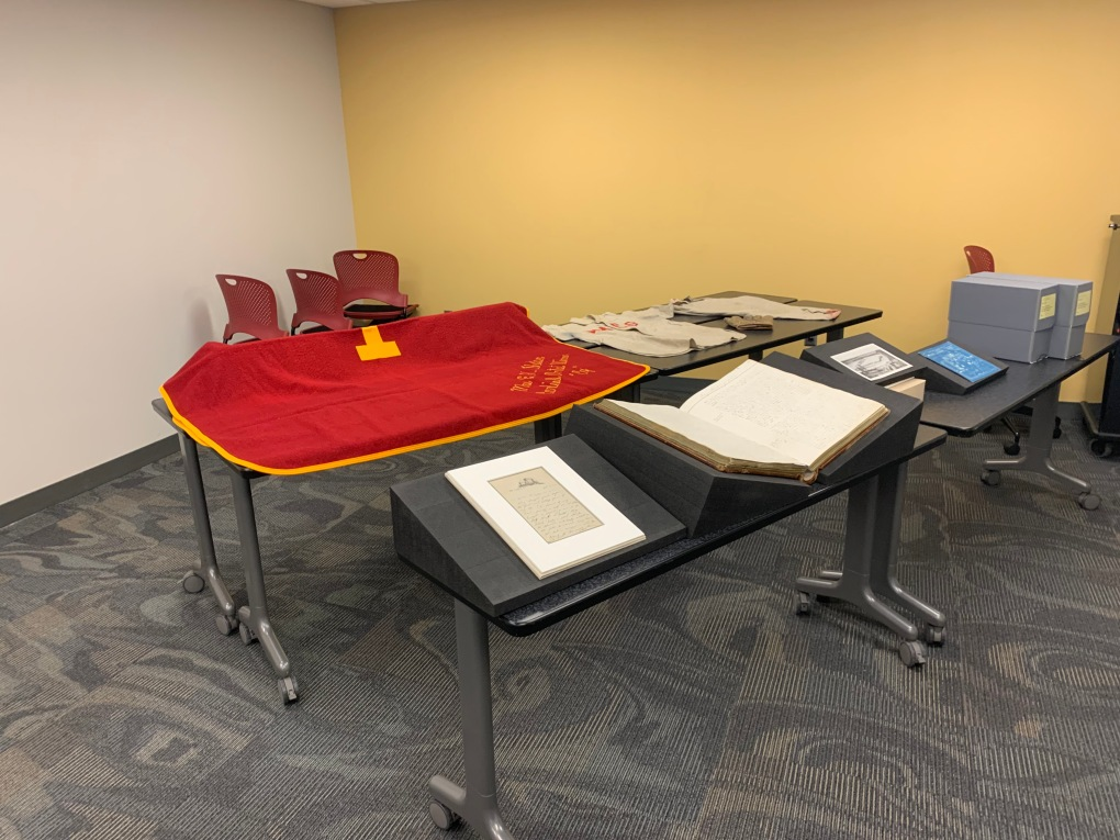4 tables filled with items from SCUA for class from University Archives includes Jack Trice's last letter, Board of Regents first minute book, 2 document boxes from Ames Lab Records, and a red blanket with Gold trim and lettering from the Artifacts Collection.