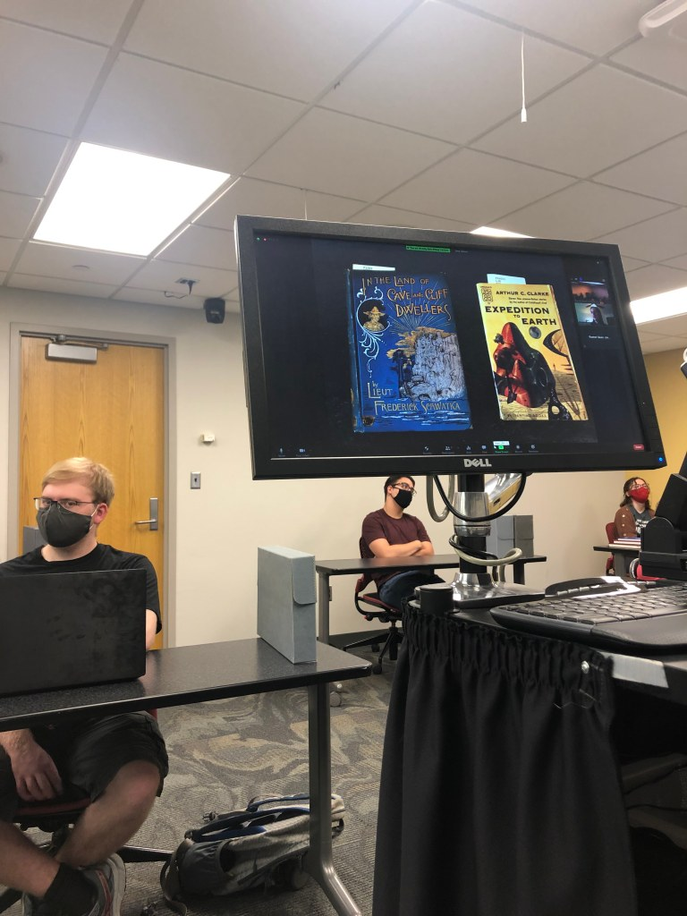 Screen showing Zoom presentation with 2 illustrated book covers showing students socially distanced wearing masks in background.