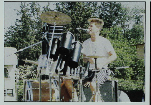 Color photograph of a drummer sitting at a drumset while singing into a microphone.