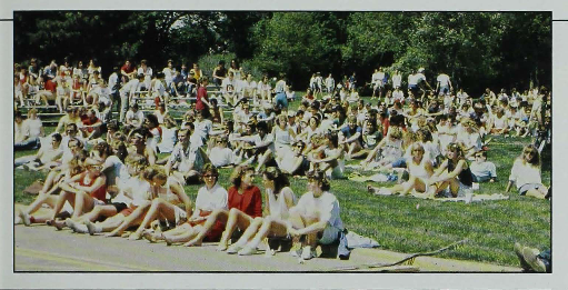 Color photograph of a large crowd of students sitting on grass.
