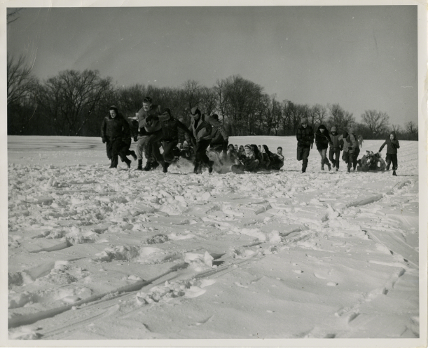 Black and white image of a group of students running in the snow, pulling another group of students behind them.