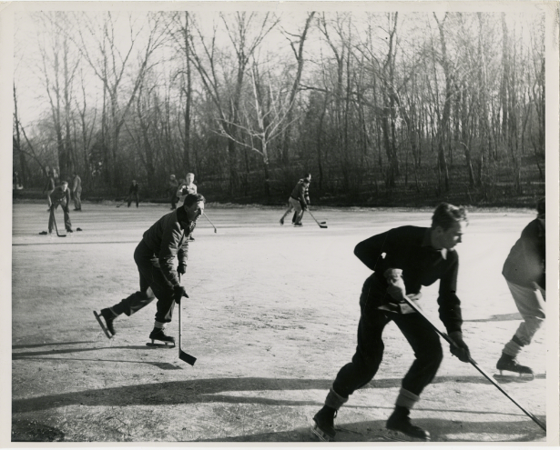 Black and white image of almost a dozen male students playing hockey outdoors, wearing ice skates.