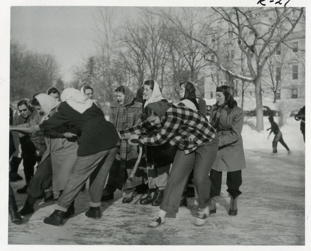 Black and white image of a group of female students pulling a rope in a game of tug-o-war, as some students skate in the background.
