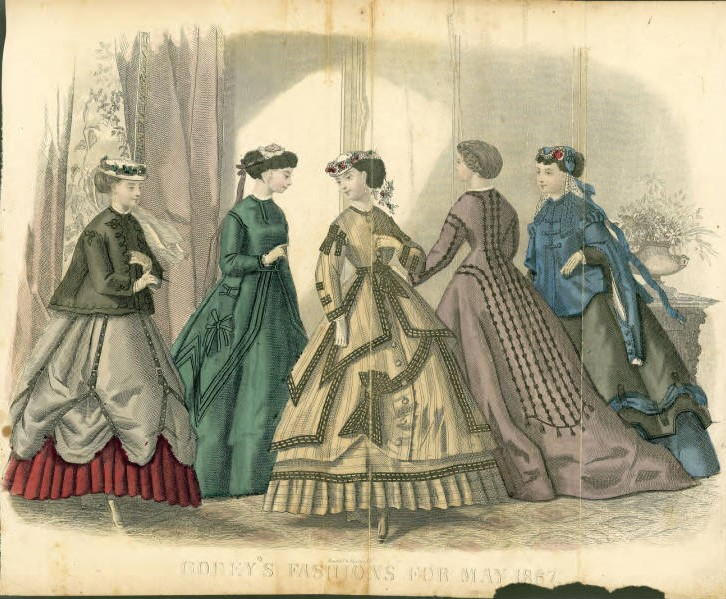 """Colorful fashion illustration on yellowing paper. The paper is torn in the bottom right hand corner. The text reads """"Codey's Fashions for May 1867"""" and depicts a group of five women in luxurious day dresses."""