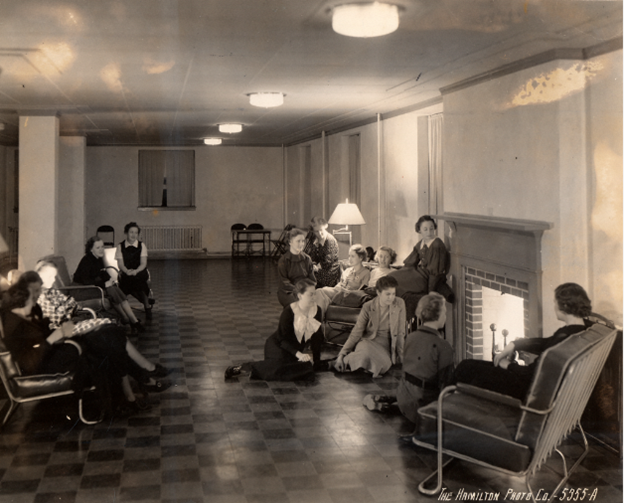 """Black and white photograph of a dozen or so young women gathered around a fireplace. Some are sitting on the floor, others in chairs. At the bottom right corner there is text that reads: """"The Hamilton Photo Co. - 5355-A""""."""
