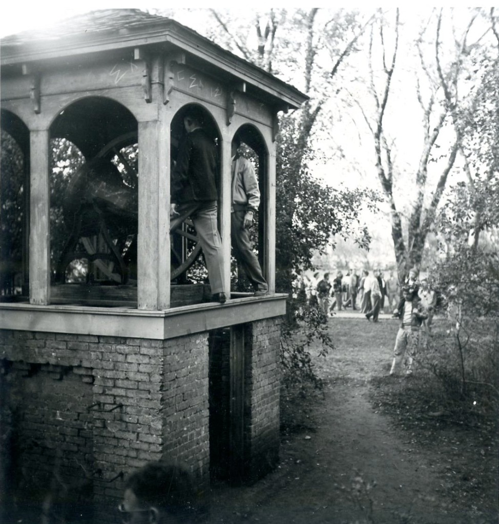 Photo of fans ringing the Victory Bell after a football win.